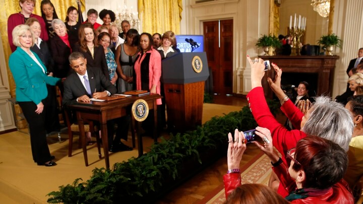 Obama Signing an Executive Order with Women Legislators Standing Behind Him